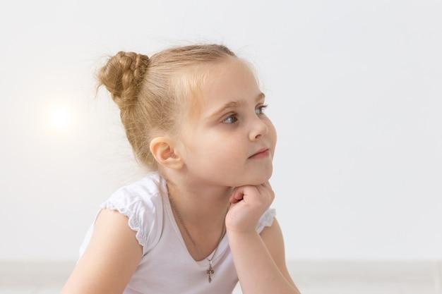 手と彼女のあごを保持している美しい小さな子供の女の子の子供と子供たちのコンセプトの肖像画