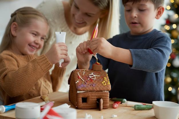 ジンジャーブレッドハウスを飾る子供と母親