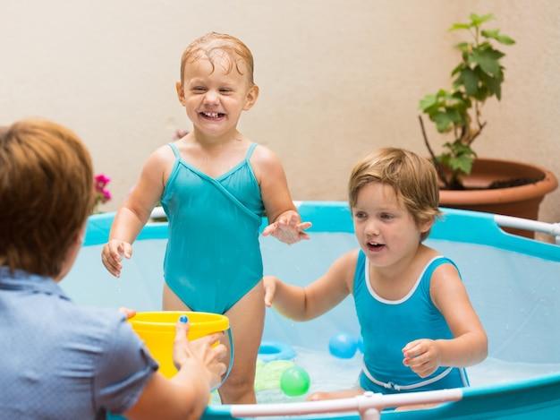 子供とプールで遊ぶ母親