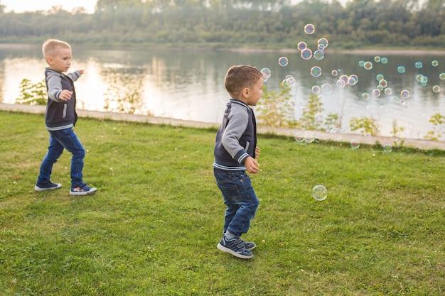 子供と自然の概念-シャボン玉を捕まえようとしている弟