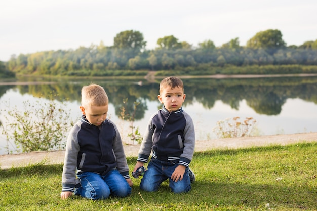子供と自然の概念-自然の背景の上に草の上に座っている2人の兄弟。