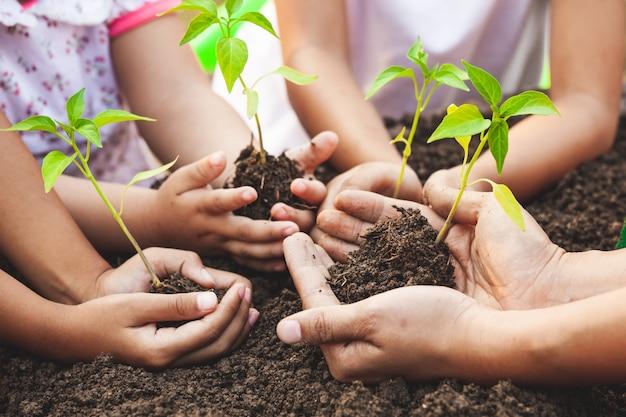 子供と一緒に黒い土に植えるための手で若い木を保持している親