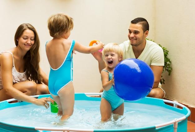 子供とプールで遊んでいる両親