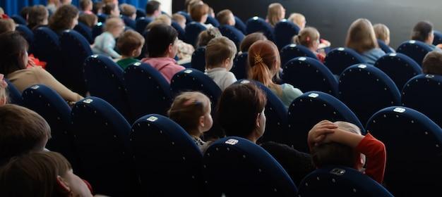 공연을 관람하는 아이들과 학부모들. 극장에서 관객입니다.