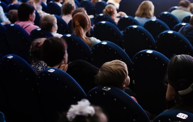 연극 공연을 관람하는 아이들과 부모들. 극장에서 관객입니다.