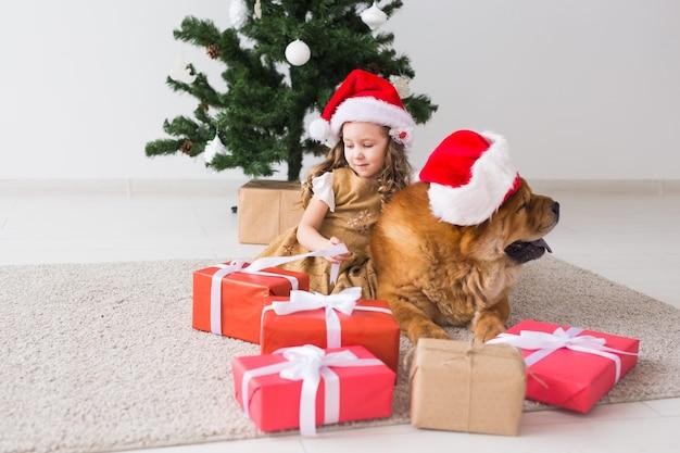 Концепция детей и домашних животных - милая девушка с собакой чау-чау, сидящей возле елки. веселого рождества и счастливых праздников.