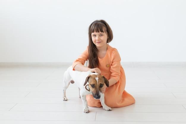 子供とペットのコンセプト-オレンジ色のドレスを着た小さな子供の女の子がジャックラッセルテリアと遊ぶ
