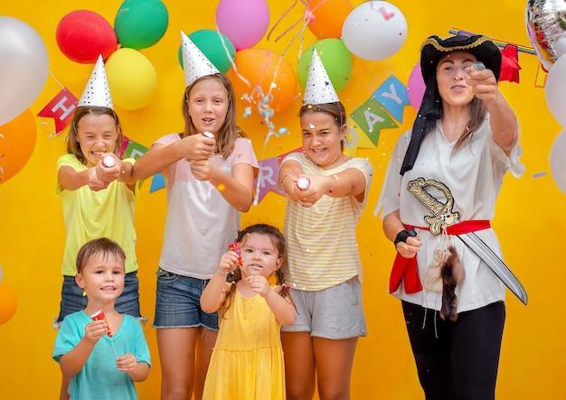 黄色の背景の誕生日パーティーで子供と海賊