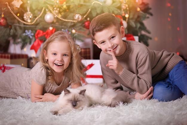 Дети и спящий кот в украшенной рождественской комнате