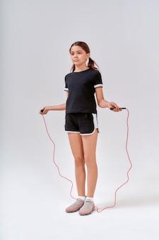 아이들과 스포츠 전체 길이의 한 귀여운 10대 소녀가 줄넘기를 들고 뛰어다니는 모습