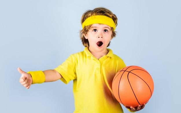子供とスポーツ、ボールを持ったスポーツウェアの小さなバスケットボール選手、バスケットボールをしているスポーツユニフォームの小さな男の子。