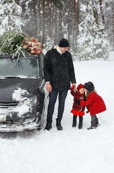아이들과 그들의 아버지는 선물과 함께 차 지붕에 크리스마스 트리를 들고 있다