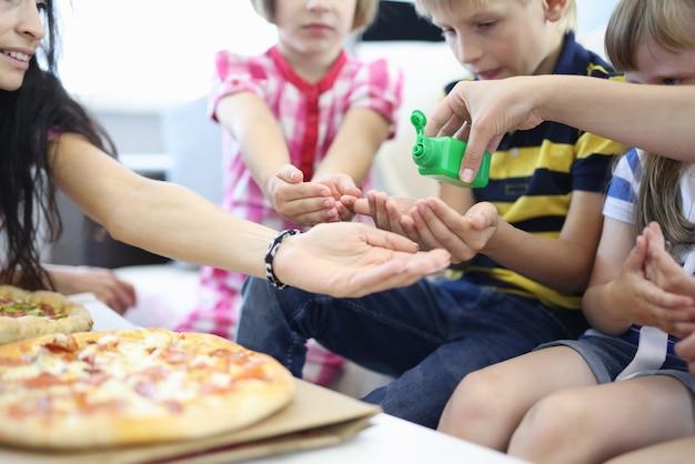 Дети и женщина сидят на диване и протирают руки дезинфицирующим средством рядом с пиццей.