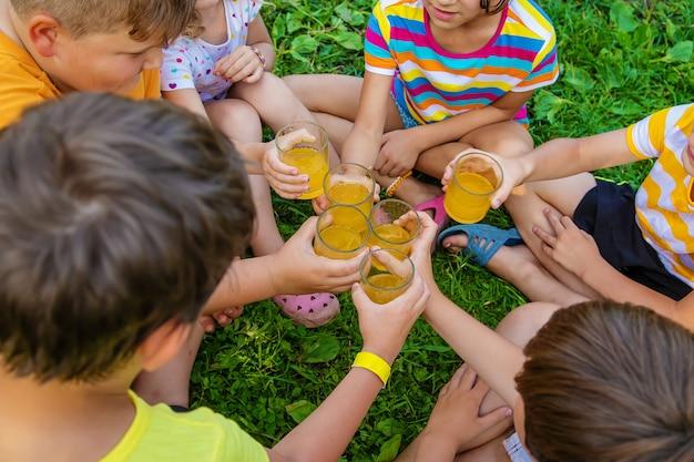 子供たちは一緒に路上でレモネードを飲んでいます。