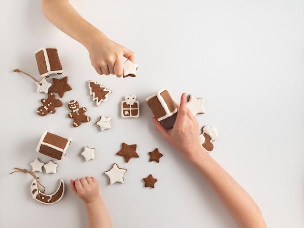 子供たちはクリスマスの準備をしています。ジンジャーブレッドクッキーと3人の子供の手。上面図。