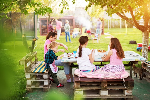 Children are having a picnic meal at the table under the tree