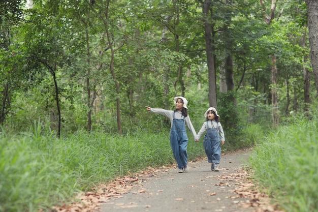 子供たちは森の中の家族のキャンプ場に向かっています。観光ルートに沿って歩きます。キャンピングロード。家族旅行の休暇の概念。