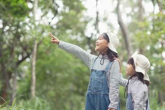 子供たちは観光ルートに沿って森の中を歩く家族のキャンプ場に向かっています。キャンピングロード。家族旅行の休暇の概念。
