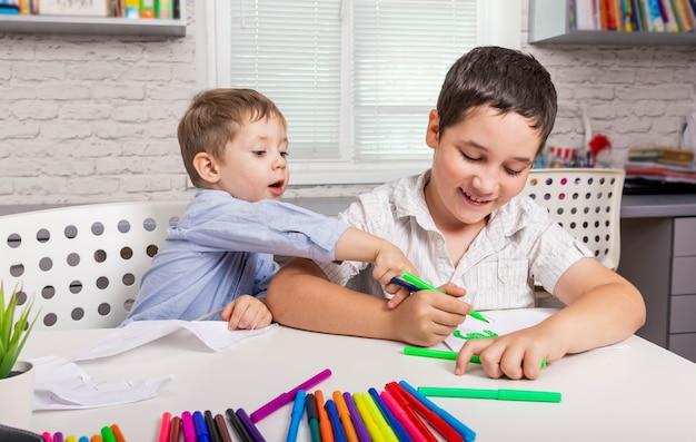子供たちは幼稚園で絵を描いています子供たちは一緒に家で描きます
