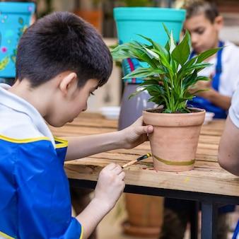 子供たちは陶器で作られた鉢植えの植物をクローズアップで描いています