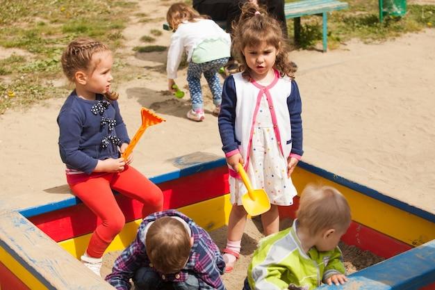 아이들은 샌드박스에 모래를 가지고 놀이터에서 놀고 있다