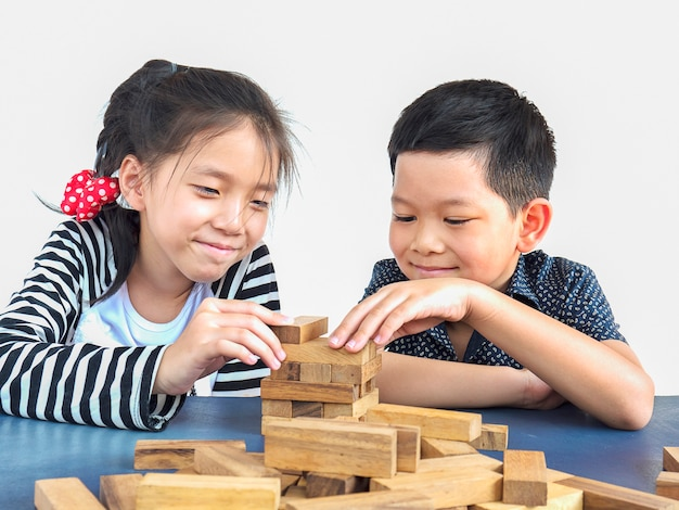 Children are playing jenga, a wood blocks tower game