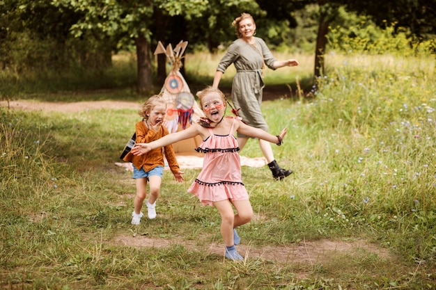 Children are playing outdoors with their mom. family is dressed in boho style, sisters have native american's makeup on faces.