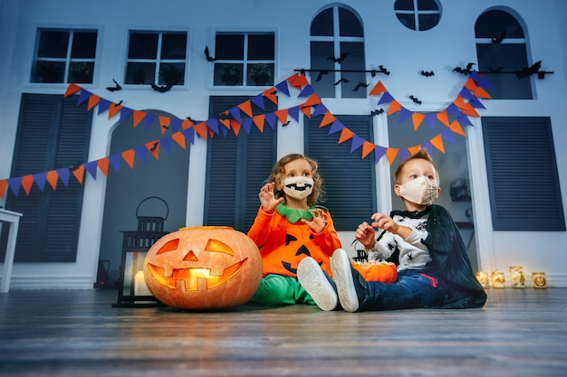 Children are playing trick or treat in halloween costumes and face masks at a festival.