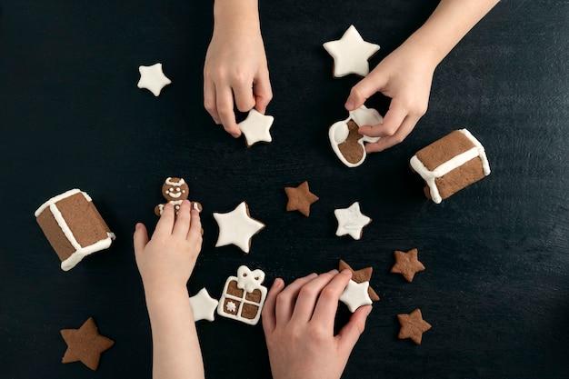 子供たちはクリスマスのジンジャーブレッドクッキーで遊んでいます。黒の背景に上面図。