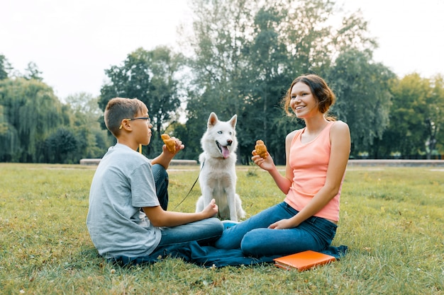 Children are resting in the park on green lawn with a white dog husky, eating croissants, talking