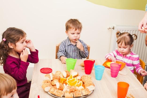 아이들은 점심과 함께 테이블에 앉아 과일과 케이크를 먹고 있습니다