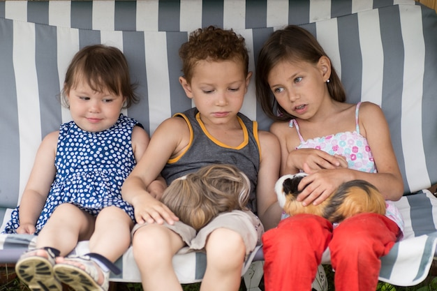 Children are sitting in a hammock and playing with guinea pig