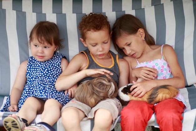 Дети сидят в гамаке и играют с морской свинкой
