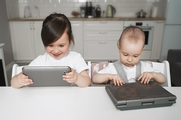 Children are sitting with gadgets. remote education for children. girl sitting with a tablet and laptop. modern digital childhood. children watch cartoons a lot