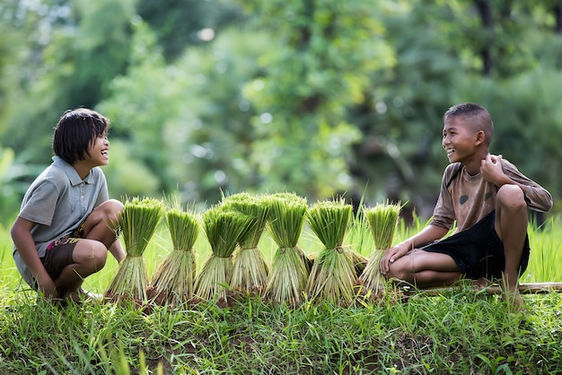 The children are smiling while they are resting beside rice sprouts.