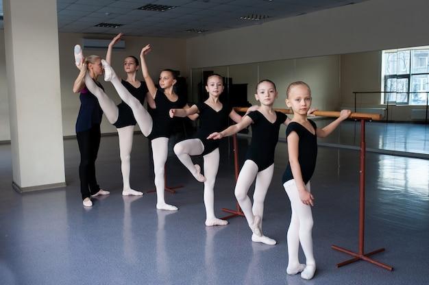 子供たちは振付のバレエの位置を教えられています