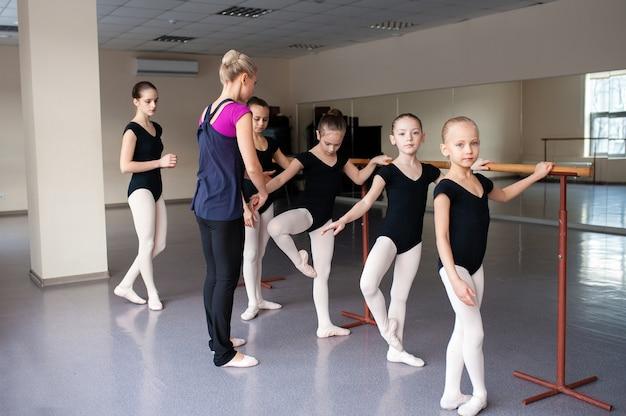 Детей обучают балетным позициям в хореографии.