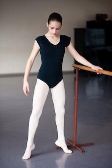 Детей учат балетным позициям в хореографии.