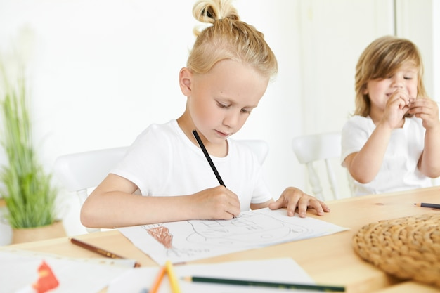Children, art, creativity and hobby concept. concentrated blonde schoolboy in white t-shirt holding black pencil, drawing something diligently, his little sister smiling sitting next to him at desk