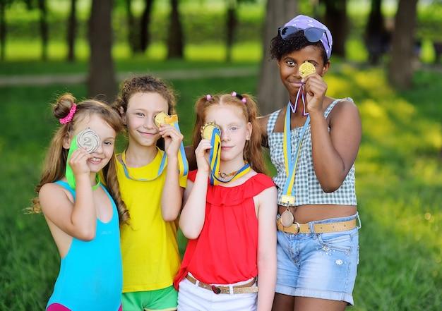 대회에서 우승한 어린이 운동선수들은 메달을 손에 들고 눈에 대고 미소를 짓습니다. 스포츠 업적.