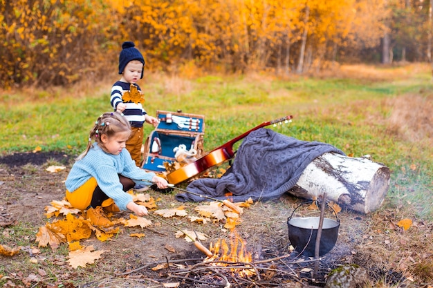 Children in the autumn forest on a picnic grill sausages and play the guitar