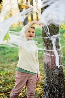 Children in autumn park, a spider web on on the tree.