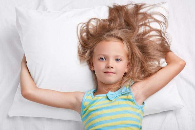 어린이, 각성 및 취침 시간 개념. 작은 사랑스러운 편안한 소녀, 캐주얼 복장을 입고 편안한 침대에서 편안한 느낌, 카메라에서 직접 파란 눈으로 보임, 어머니에게 좋은 아침이라고 말합니다.