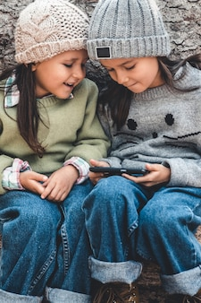 Children in the background of logs play with a smartphone. watch the video and have fun. friendship, sisters, family.