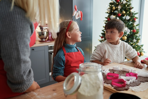 クリスマスの時期にジンジャーブレッドのクッキーを焼く子供たち