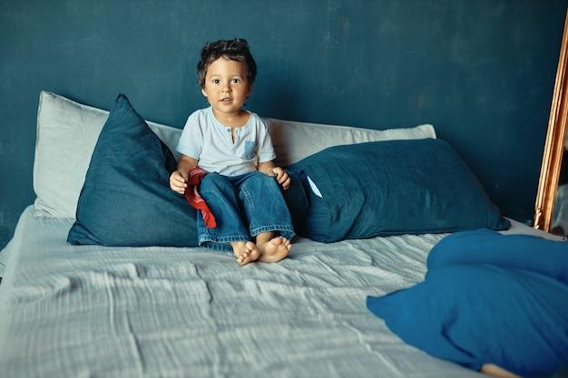 子供、寝具、子育てのコンセプト。ベッドに座って、昼間の睡眠の後に遊ぶ準備ができているかわいい裸足の混血の小さな男の子。