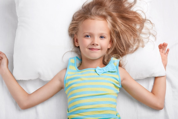 Children, bedding and awakening concept. pleased small european girl with charming tender smile, long light hair, dressed in pajamas, lies on white pillow and bedclothes, has appealing appearance.