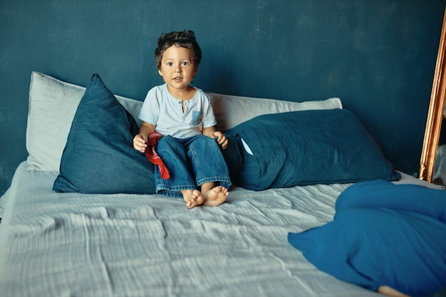 Children, bedding and parenting concept. cute barefoot mixed race little boy sitting on bed, ready to play after daytime sleep.