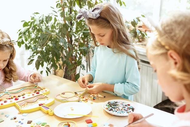 I bambini e le decorazioni di compleanno. i ragazzi e le ragazze a tavola apparecchiano con cibo, torte, bevande e gadget per la festa.