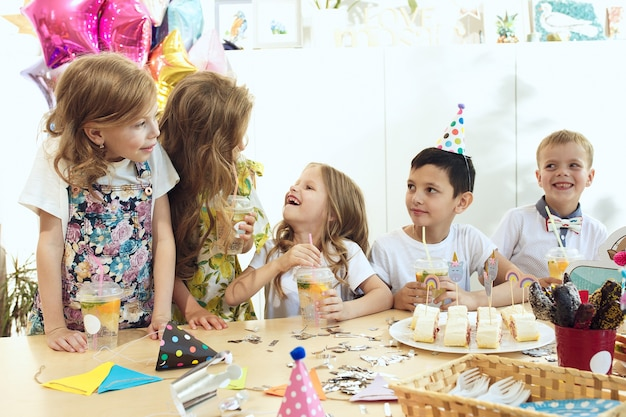 Children and birthday decorations. boys and girls at table setting with food, cakes, drinks and party gadgets.